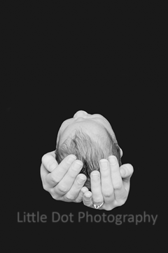Newborn baby head in hands